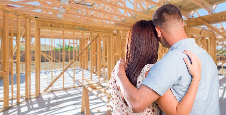 Young Military Couple On Site Inside Their New Home Construction Framing.